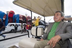 Foto de joasinho Trinta em um carro de golf nos bastidores de uma escola de samba.