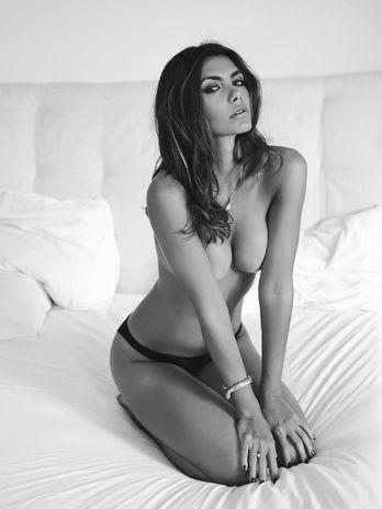 LFilha do datena de joelhos na cama sentada sobre os pés